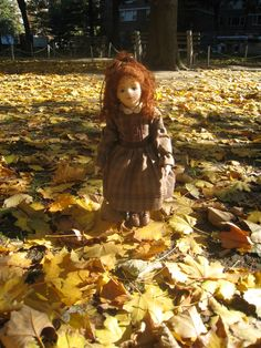 Molly, a hand-made, molded-face felt doll, in the autumn leaves.