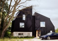 Mole Architects has completed a house in Poole, comprising a pair of blackened timber volumes that resemble the upturned hull of a boat