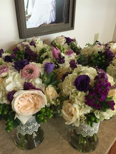 Bridesmaids bouquets doing double duty as reception centerpieces. Roses, ranunculus, tulips, hydrangea, and wax flower