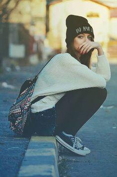 De toca, mochila, sentada na calçada