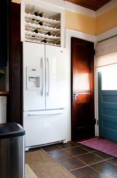 Kristen & Michelle's Modern Bohemian kitchen.  Wine rack in space above refrigerator.