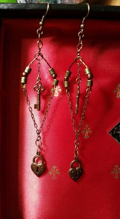 These beautiful vintage style earrings feature a heart lock, and key dangling from a metal frame. The metals used in these earrings are all nickel free