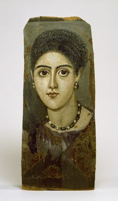 """2nd century AD Fayum encaustic (wax, pigments, cloth, wood) of female at Walters Art Museum in Baltimore (Acc. 32.5).  By hair style, dated to Trajanic (98-117 AD). Note emerald and pearl earrings and necklace. 17 5/16"""" h x 7 7/16"""" w x 9/16"""" thick (44 x 18.9 x 1.4 cm)."""