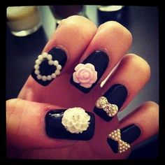Feminine 3D nail art on black nails. Each nail has something special: a heart, rose, bow, and white flower.