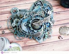 """""""I made a steampunk style canvas using art alchemy paints and waxes. The shine they give over black gesso is amazing. I combined a heart and star-shaped canvas, then decorated it with some Finn's mechanical embellishments and IOD molds."""" ~ Ola"""
