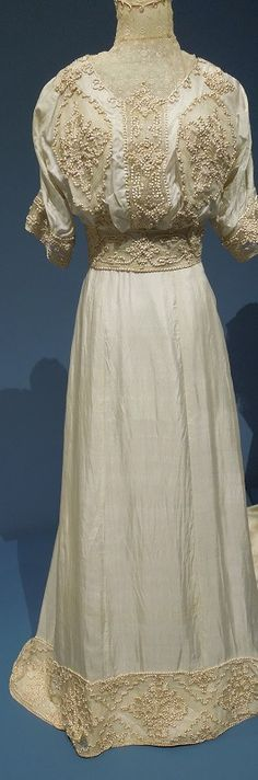 """""""Complex works of art,"""" curator Sheryl Peters said of wedding gowns dating from about 1906 to 1915.  In this, our first dress, the lace around this collar is the most delicate I have ever seen.  It looks as if it would dissolve if I breathe on it.  Silk cord runs just above it, at the top of the collar, and also below the lace.  It is looped.  That same silk cord is pulled through net elsewhere on this dress to make elaborate designs on the bodice, cuffs and the belt."""
