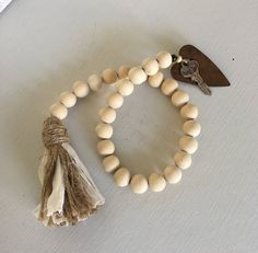 This wood bead garland is crafted with natural wood beads and strung on natural jute with a rag and jute tassel and rusty heart and key. Add a little rustic farmhouse touch to your home. Wood Bead Garland, Beaded Garland, Handmade Keychains, Handmade Jewelry, Beaded Crafts, Diy Crafts, Passementerie, Homemade Christmas Gifts, Wood Ornaments