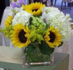 Flower delivery in North Arlington by North Arlington florist - sunflowers solidago carnation and hydrangea with stones on the bottom of vas...
