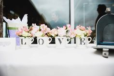 Displaying flowers in jars/vases/cups with lettering makes for amazing photos and wedding decor. L.O.V.E
