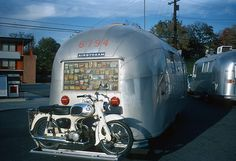 Motorcycle on the back of a vintage camping trailer
