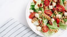 Overhead, close-up shot of BLT pasta salad with crispy bacon, grape tomatoes, green leafy lettuce and fresh mozzarella in white bowl with blue striped linen. Shutterstock ID Purchase Order: N/A Asian Pasta Salads, Mediterranean Pasta Salads, Caprese Pasta Salad, Summer Pasta Salad, Blt Salad, Healthy Picnic Foods, Healthy Recipes, Salad Recipes Video, Pasta Salad Recipes