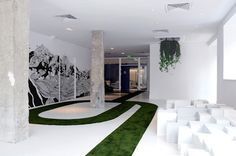 Green pathways snake across the floor of the lobby while clusters of white blocks provide informal seating.