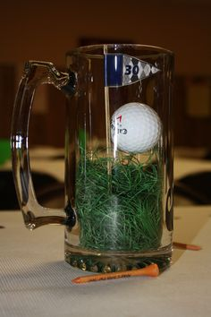 I made this centerpiece for my husbands 30th birthday. Mug w/ faux grass, golf ball glued on custom tee and homemade flags with a design from esty creator MetroDesign. I also added a mustache sticker to the other side.
