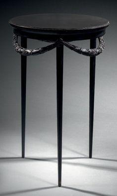 Paul Iribe  (1883-1935) - Guéridon en  ébène du Gabon à plateau circulaire intégrant une dalle de marbre noir de Belgique en léger ressaut ornementé d'une ceinture détachée formant guirlande entièrement sculptée de fleurs et feuillages. Piètement à trois jambes circulaires fuselées. Estampillé et daté 1914. - H: 71 cm