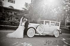 Bride and Groom with old white vintage car parked out front of the Hyatt Regency Huntington Beach | Lisa Simpson Weddings | Jim Kennedy Photographers