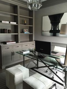 A desk made of glass and metal is functional and stylish in this home office without feeling bulky or visually crowding the room. Gray built-ins add character and storage to the space.