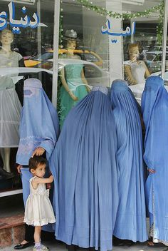 Afghan girls clad in Burqas, window shopping at the wedding dress shop, Kabul, Afghanistan.