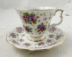Made by Royal Albert, this tea cup and saucer is white and covered with pink and purple flowers. Gold trimming on cup and saucer edges. Pattern is called Richmond and is part of the Nell Gwynne Series.  Excellent condition (see photos).  Markings read:  Royal Albert Bone China England Nell Gwynne Series Richmond     Please bear in mind that these are vintage items and there may be small imperfections from age or flaws from production. I try to make my photos as clear as possible and…