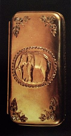 Gold cigarette box embossed with elephant design decorated with diamonds.
