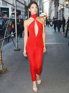 Lily Aldridge wears a red halter cutout jumpsuit with nude heels