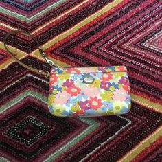 Coach Wristlet Floral Print Coach wristlet in floral print measures 7.5 inches wide by 5 inches tall. My iPhone 6s fits with room to spare. Has front pocket and inside has one little pocket for credit cards or ID. Has been used but in good condition. Coach Bags Clutches & Wristlets
