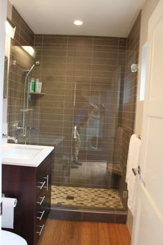 Chic tiny bathroom... feels pretty big to me! Like hardwood floor, light vanity top with dark vanity and silver pulls. Like cream cabinet opposite commode and taupe subway tile...overhead lighting, and now shower surround even tho raised shower sill.