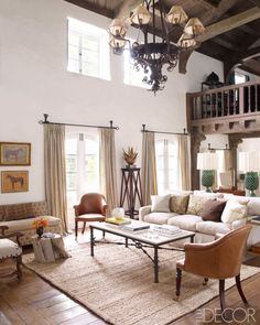 The 19th-century leather chairs in the living room are English, the sofa is by Buckingham, and the settee is upholstered in a Rogers & Goffigon velvet; the small table is made from an apple-tree stump, the curtains are of a cotton from Claremont, and the jute rug is by Pottery Barn.   - ELLEDecor.com