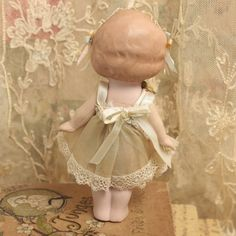 This adorable little bisque doll wears her original organdy lace and ribbon trimmed dress that has been accented with a spray of old ribbon work roses. Her headband is a perfect compliment to the dress, made from vintage multicolored lace and vintage silk ribbons. She measures 6 inches tall. She was made in Germany, making her more rare than the little Japanese dolls you usually see. In excellent condition, she has reticulating arms. She leans ever so slightly to the left as this is the way…