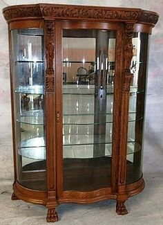 Quarter Sawn Or Tiger Oak Curved Glass China Cabinet With Well Carved Griffins Atop Pilasters Flanking The Serpentine Shaped Door, Crown Is Fully Carved Leafy Foliage On A Stippled Background, Feet Are Carved Paws   c.1890