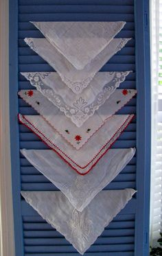 vintage handkerchiefs tucked into louvre doors- thought of a friends Mom who collected hanker-chiefs