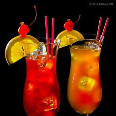 Two Hurricane Cocktails in Hurricane Glasses with Orange and Cherry Garnish. ☀CQ #mardisgras #southern #recipes