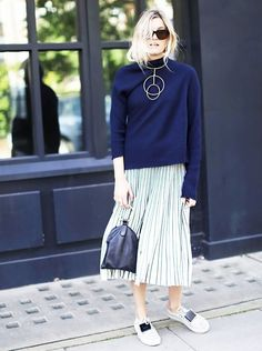 Camille Charrière wears a turtleneck sweater, pleated midi skirt, sneakers, a statement necklace, and mini bag
