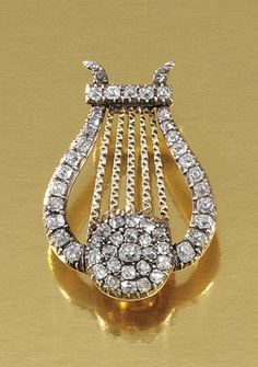 DIAMOND BROOCH, EARLY 19TH CENTURY.  Designed as a lyre, set throughout with foil-backed circular-cut diamonds.