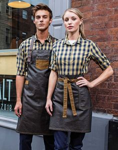 Premier Workwear Division Waxed Look Bib Apron & Division Waxed Look Waist Apron in Black/Tan. Paired with Long Sleeve Mulligan Check Cotton Bar Shirt in Camel/Navy Cafe Uniform, Waiter Uniform, Hotel Uniform, Staff Uniforms, Work Uniforms, Kellner Uniform, Chef Dress, Cafe Apron, Jean Apron