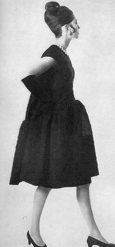 1965 - Balenciaga's black cloqué ruffled tunic swinging freely over black satin, curved waistline and short capped sleeves as seen in Vogue