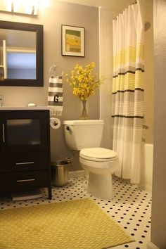 gray and yellow bathroom – love the mix of the white subway tile, the white  black penny tile and the stripes on the curtain and towel.
