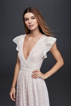 The bohemian, flutter-sleeve dress that Lauren Bushnell modeled for her gorgeous, outdoor engagement session with Bachelor Ben Higgins is finally available for purchase. The ivory and blush piece—a crinkled chiffon gown that features flutter sleeves and tiny embroidered blossoms—is listed on the David's Bridal website for $289.95.