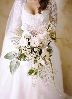 A cascading bouquet of roses, snowberries, lisianthus, calla lilies, and orchids, surrounded by ivy and eucalyptus leaves | Brides.com