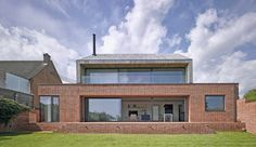 Rear view of the house at Broad Street in Suffolk by Nash Baker Architects, showing the local handmade red bricks used on the ground floor, and the oak cladding wrapping around the first floor.