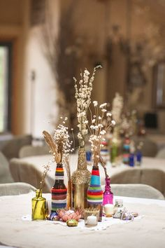 Wrapped bottles to double as centerpieces... Not with yarn, but paint and glitter on wine bottles could make a great and inexpensive centerpiece!!: