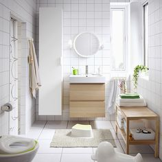 A medium size white bathroom with wall cabinets in white and white stained oak effect.