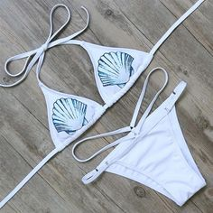 Channel your inner ocean goddess in this sexy white two-piece. Seashells accent the adjustable classic triangle top, while the bikini bottoms feature a playful hip-hugging strap.