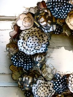 paper flowers wreath. I could easily re do this with scrapbook paper, scissors, hot glue, cute buttons, and plumbing tube for the wreath (0.97 cents at lowes)