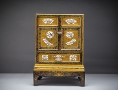 FINE GOLD LACQUER AND IVORY KODANSU (CABINET), MEIJI PERIOD (1868-1912) Of rectangular form decorated with inlaid ivory, the hinged door opens to reveal six drawers fitted with silver bird pulls. Dimensions: Height 14 3/4 in. (37.5 cm.)