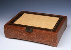 """This handsome Jewelry boxis created from South American leopardwood.The body is joined by leopardwood """"butterfly"""" splines. The lid is a curly maple veneered panel framed in wenge with a cherry and wenge inlay banding. The lift tab is solid black palm.The dividers and lift out tray are cherry, curly maple and leopardwood. The tray and bottom are lined with plush black velvet This box is signed and all the woods used are listed on the bottom.  Size 14 x10 x 4, Woods; leopardwood, cu..."""