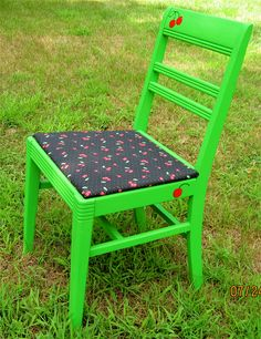 Vintage wooden kitchen chair repainted apple green.  The fabric is a vintage cherry print on black background.  Hand painted red cherries pop on the green background.  For sale at $69.