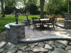 Multi-level brick paver patio in Glenview, IL with curved seat walls, accent columns and outdoor lighting. Custom designed and built by Archadeck of Chicagoland.
