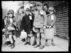 A photograph of a group of evacuees, taken in September 1938 by George W Roper for the Daily Herald.    The children, carrying a few possessions in brown-paper parcels and bags, are moving for safety from Haverstock Hill School in Hampstead, London, to the countryside. Each child wears a ticket on their coat to identify them in the event of their being lost.