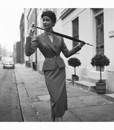 A model wearing a tailored suit by Simon Massey, with gloves and an umbrella, 1953