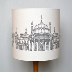 A beautifully handmade lampshade featuring an illustration of the Royal PavilionThis Pavilion lampshade is part of Joanna's Brighton range, which was born from her love of architecture and cities, capturing their unique culture and style within her designs. This lampshade features a detailed illustration of the famous Royal Pavilion. Each lampshade is handmade to order in a range of sizes as shown below and also for use either as a ceiling pendant or for a lamp base. This lampshade is ...